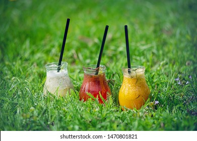 Lemonade in glass decanters with black drinking straws stands on a green lawn.
