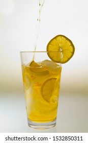 Lemonade in the Glass Filled with Fresh Lemons and Ice, Isolated on White