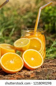 Lemonade in a glass, lemons, oranges on a tree on background of