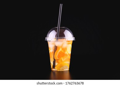 Lemonade to go cup with mint, orange and lemon on black background, isolated