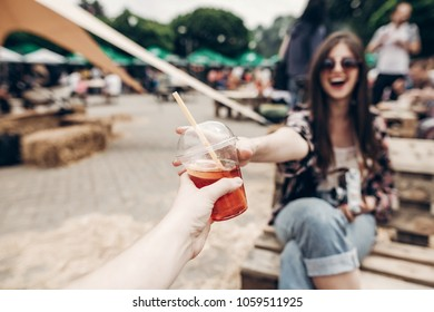 lemonade in hand. man giving lemonade to stylish hipster woman in sunglasses with red lips. cool boho girl with cocktail at street food festival. summer vacation, space for text