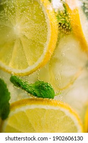 Lemonade with ice and mint in a glass glass on a wooden table