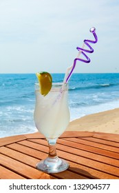lemonade with ice on the table against the background of sea and sky
