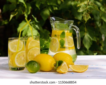 Lemonade in the jug, lemon, lime, two glasses and mint on white wooden table.