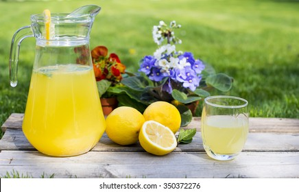 Lemonade in the jug and lemons on the table outdoor