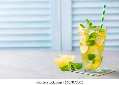 Lemonade, lemon ice tea, mint cocktail in glass. Blue background. Close up. Copy space.