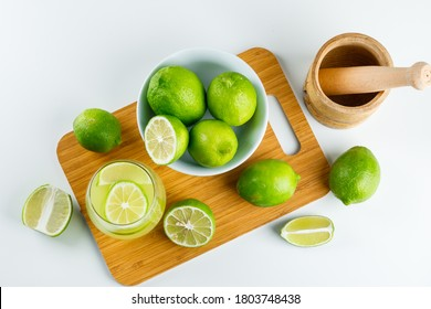 Lemonade with lemon, mortar and pestle in a glass on white and cutting board background, flat lay.