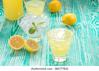 lemonade or limoncello in glasses with ice cubes, sherbet glass with ice cubes decorated by mint leaf, lemon fruits on turquoise colored wooden table