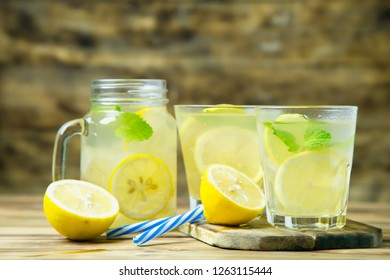 Lemonade or mojito cocktail with lemon and mint on wood background