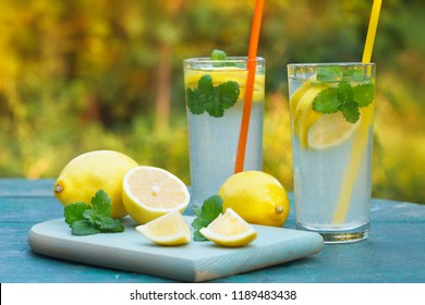Lemonade or mojito cocktails in the glasses with lemon slices and mint on the table outdoor