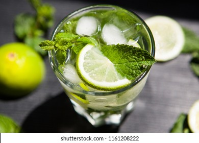 Lemonade or Mojito coctail with lime, mint and ice, fresh drink on black table