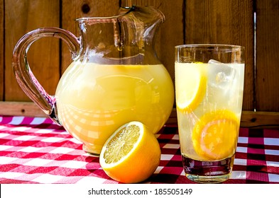 Lemonade and pitcher with sliced lemons on red gingham table cloth.