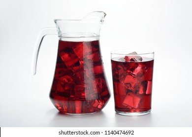 Lemonade or red summer in a jug and a glass with ice on white background