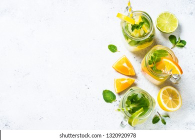 Lemonade set. Lemonade, mojito and orange lemonade. Iced summer drink in mason jar with ingredients on white table top view.