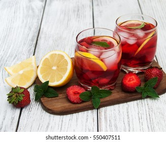 Lemonade with strawberries, lemon and mint on a old wooden table
