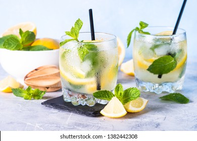 Lemonade. Summer cold drink with lemon, mint and ice on light table.