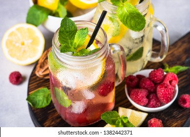 Lemonade. Two lemonades - classic and strawberrry in mason jars with ingredients. Close up.