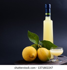 Lemoncello in a bottle on a black background, Traditional Italian liqueur from lemons. Alcohol yellow and fresh lemon with green leaves. Place for text,