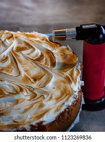 a lemoncheesecake with swirly burned merengue with a small red kitchen flamethrower/burner on the right