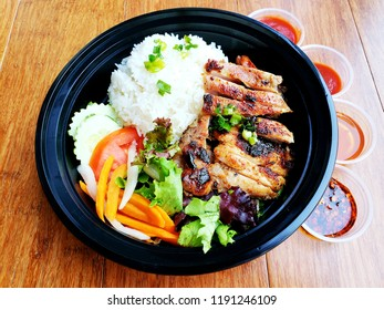 """""""Lemongrass Chicken"""" Asian food, Grilled Chicken with Lemongrass served with rice, salad, and pickles in plastic bowl for takeaway food also come  with 4 different kinds of sauce."""