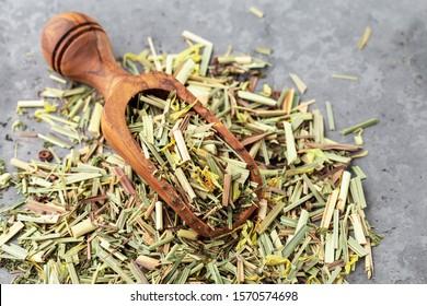 Lemongrass in a wooden shovel, on a gray background. Dry sprigs of natural lemongrass.