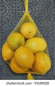 Lemons: a bag of lemons against a pierced tin background