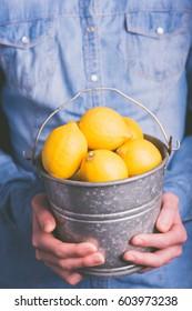 lemons bucket in hands - vegetarian and vegan people - vintage style filter