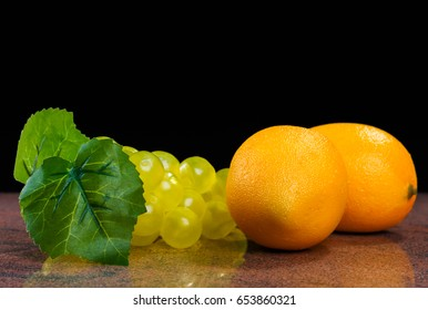 lemons and fake bunch of grapes on granite surface and black background