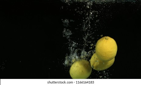 Lemons falling into water on black background. Bright high quality video. Shot 120 frames per second on BlackMagic URSA camera.