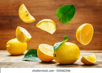 lemons with flying slices on a wood background. tinting. selective focus