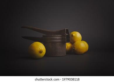 Lemons and juicer on dark background