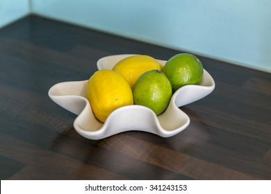 Lemons and lime in a bowl in a modern, colorful kitchen