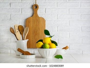 Lemons and limes in a bowl on the table in the kitchen