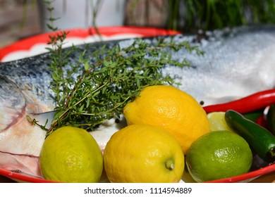 Lemons and limes next to a salmon