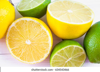 lemons and limes on a wooden background.