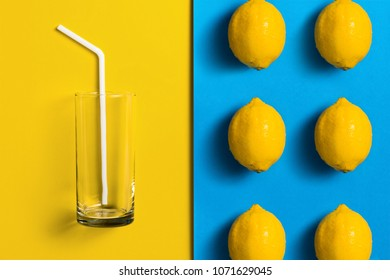 Lemons on split colored background with glass and straw.