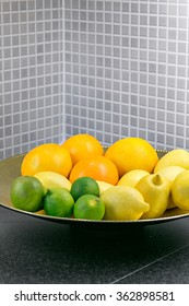 Lemons, oranges and lime in a bowl in a modern, colorful kitchen