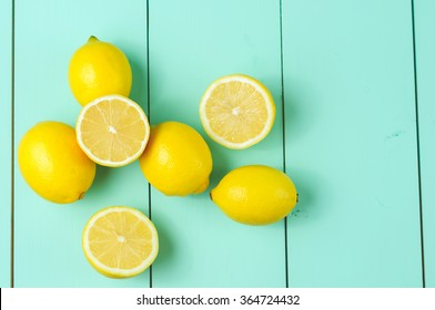 Lemons scattered on a blue wooden background.