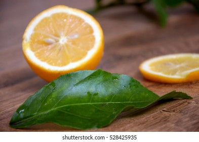 Lemons sliced with leaves. On wooden background.