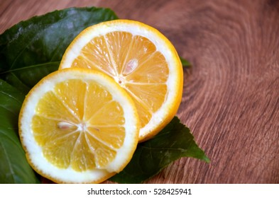 Lemons sliced with leaves. On wooden background.  Top view