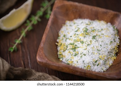 Lemon-Thyme Herb Salt in Small Wooden Bowl; Fresh sprig of herb on Wooden Tabletop beside the bowl