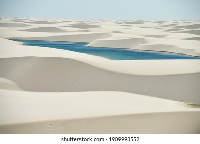 Lencois Maranhenses National Park in Brazil, low, flat, flooded land, overlaid with large, discrete sand dunes with blue and green lagoons