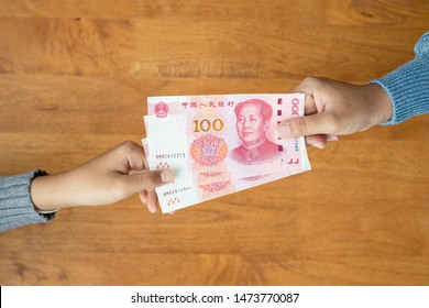Lend or Giving money concept. Top view hand giving banknote currency Chinese Yuan (CNY or RMB) for property and land business used