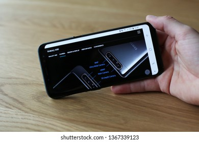 LENDELEDE, BELGIUM- APRIL 12TH 2019: Hand holding a Samsung S9 with a Samsung Galaxy A80 on the touch screen. The brand new phone features an innovative flip camera. Illustrative editorial.