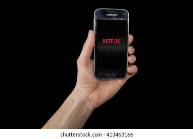 LENDELEDE, BELGIUM - APRIL 20TH 2016: a hand holding a Samsung Galaxy S5 mini mobile phone which displays the Netflix app on the touch screen. An illustrative editorial image on a black background.