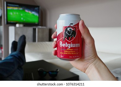 LENDELEDE, BELGIUM - APRIL 24TH 2018:A hand holding a cold Belgium beer, with soccer on the TV in the background. The brand Jupiler changed its name for the UEFA FIFA World Cup. Illustrative editorial