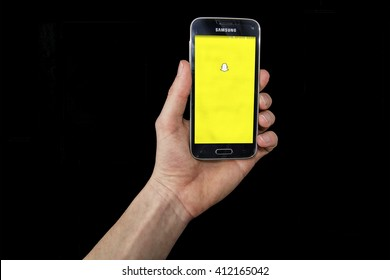 LENDELEDE, BELGIUM - APRIL 26TH 2016: a hand holding a Samsung Galaxy S5 mini mobile phone which displays the Snapchat app. Illustrative editorial image on a black background.