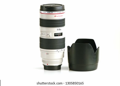 LENDELEDE, BELGIUM - APRIL 27TH 2018: An isolated Canon EF 70 200mm F2.8 L USM lens, standing upright next to the lens hood on a white background. The fast glass is very popular.Illustrative editorial