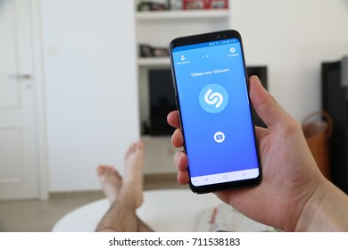LENDELEDE, BELGIUM - AUGUST 26TH 2017: a hand holding a new Samsung Galaxy S8 mobile phone which displays the Shazam app. Illustrative editorial image on an interior background with feet on the table.