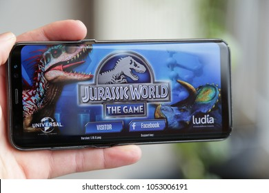 LENDELEDE, BELGIUM- FEBRUARY 24TH 2018: hand holding a new Samsung S8 phone which displays the Jurassic World Alive game app on the touch screen. Illustrative editorial image on an interior background